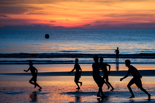 playing football at the beach